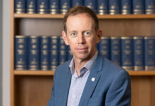 Unsmiling, ACT Attorney-General Shane Rattenbury wears a blue blazer and sits in front of a wooden bookshelf with blue books.