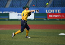 ACT Olympic hopeful Clare Warwick wears a green and gold uniform and is pictured in action, throwing a softball.