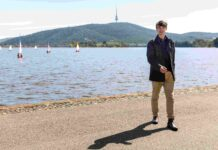 Well-dressed young man walking beside Lake Burley Griffin in Canberra with Black Mountain tower in background and sailboats on the water