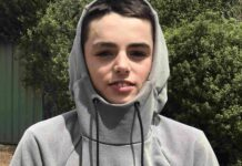 teenage Caucasian boy with dark hair wearing a grey hoodie