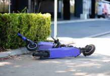 Two purple e-scooters lie on their side on a footpath