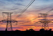 Powerlines are backlit by a colourful sunlight in this photo that accompanies a story about ACT energy retailers