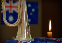 a military bugle and candle in front of an Australian flag