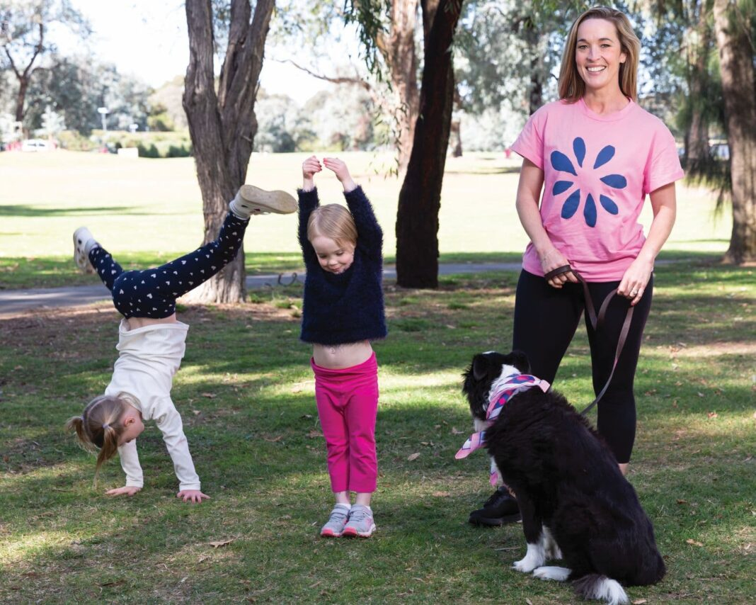 two little girls doing cartwheels as their mum in a pink t-shirt with dog on lead watches on, smiling