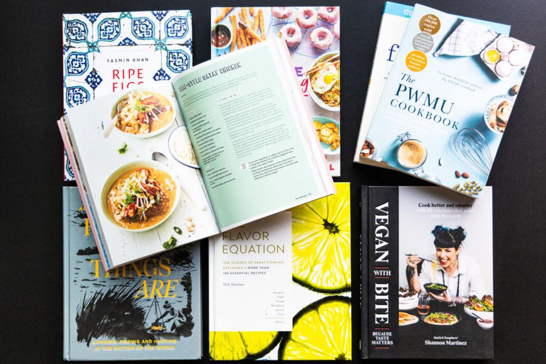 Several beautiful new cookbooks spread across a black tabletop