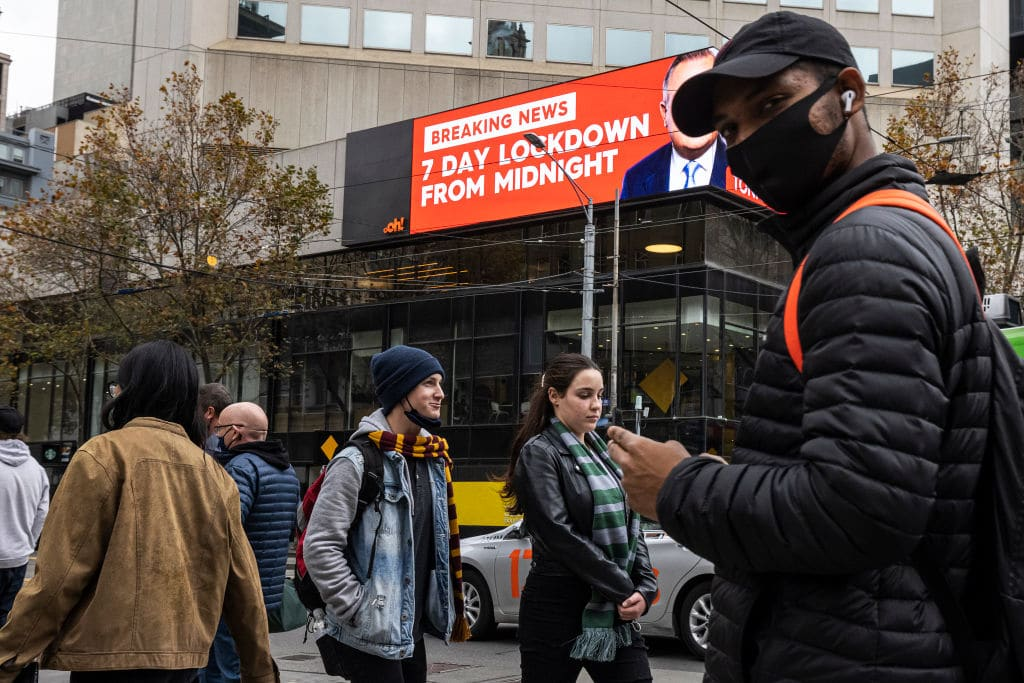 MELBOURNE, AUSTRALIA - MAY 27: People wearing face masks are seen crossing Bourke Street Mall in front of an LED sign in the background displaying news of the impending 7 day lockdown on May 27, 2021 in Melbourne, Australia. There are now 34 cases linked to a current cluster that spans several households and a workplace, with numerous exposure sites across many different parts of Melbourne and Bendigo. Victoria will go into a 7-day circuit breaker lockdown restrictions from 11:59 pm Thursday 27 May to 11:59 pm Thursday 3 June 2021. (Photo by Daniel Pockett/Getty Images)
