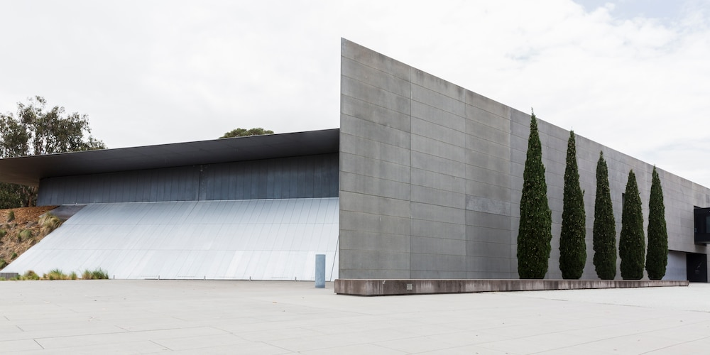 Grey concrete exterior of Anzac Hall, an award-winning architectural space at the Australian War Memorial in Canberra, flanked by a row of conifers